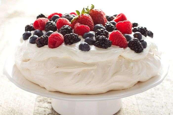 Pavlova preparada com merengue, chantilly e frutas frescas