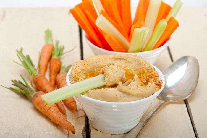 Homus servido com palitos de cenoura, pepino, salsão ou aipo